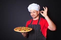 Stående av den lyckliga attraktiva kocken med en pizza i händer Arkivfoton