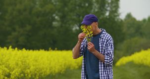 Stående av den lyckliga bonden Holding Rapeseed Blossoms på lantgården arkivfilmer