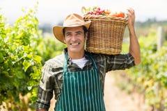 Stående av den lyckliga bonden som bär en korg av grönsaker royaltyfri foto