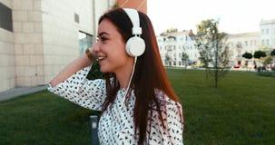 Stående av den lyckliga charmiga brunettdamen som lyssnar till musik via hörlurar och promenerar gatan längd i fot räknat 4k arkivfilmer