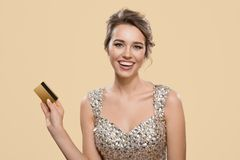 Stående av den lyckliga charmiga kvinnan som rymmer den guld- plast- kontokortet arkivfoto