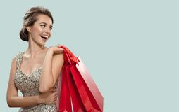 Stående av den lyckliga charmiga kvinnan som rymmer röda shoppa påsar _ arkivbilder