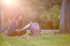 Stående av den lyckliga charmiga thailändska kvinnan som läser en bok royaltyfri foto