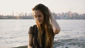 Stående av den lyckliga europeiska flickan med flyghår som poserar som ler på kameran på solnedgångstranden med New York City hor arkivfilmer