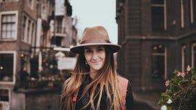 Stående av den lyckliga europeiska flickan som ser kameran Attraktiv ung dam i kall hatt med långt le för flyghår 4K lager videofilmer