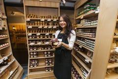 Stående av den lyckliga försäljarevisningprodukten i livsmedelsbutik fotografering för bildbyråer
