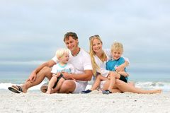 Stående av den lyckliga familjen av fyra personer som kopplar av på stranden Royaltyfri Fotografi
