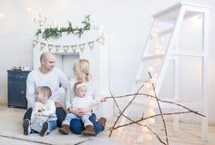 Stående av den lyckliga familjen av fyra som hemma sitter på golv i vitt rum Arkivbild