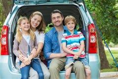 Stående av den lyckliga familjen av fyra som sitter i bilstam Arkivbild