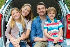 Stående av den lyckliga familjen av fyra som sitter i bilstam Fotografering för Bildbyråer