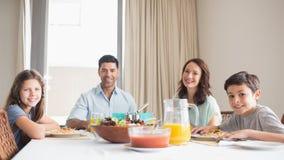 Stående av den lyckliga familjen av fyra som sitter på att äta middag tabellen Arkivbild
