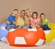 Stående av den lyckliga familjen av fem som har gyckel i ett rum royaltyfria foton