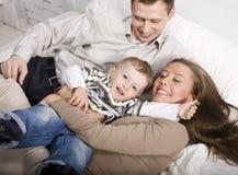 Stående av den lyckliga familjen, mamman och farsan som spelar med deras son i säng Arkivfoto