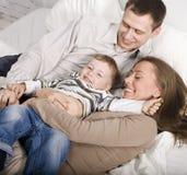 Stående av den lyckliga familjen, mamman och farsan som spelar med deras son i säng Arkivbilder