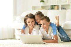 Stående av den lyckliga familjen med bärbara datorn Arkivfoton