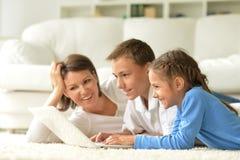 Stående av den lyckliga familjen med bärbara datorn Royaltyfri Foto