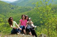 Stående av den lyckliga familjen med en hund i det gröna berget arkivbilder