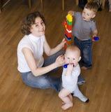 Stående av den lyckliga familjen, moder som spelar med söner Arkivbild
