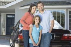 Stående av den lyckliga familjen mot bilen och hus Fotografering för Bildbyråer
