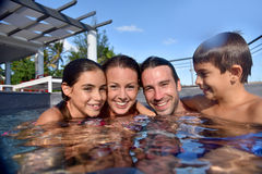 Stående av den lyckliga familjen på sommarferier i pöl royaltyfria foton