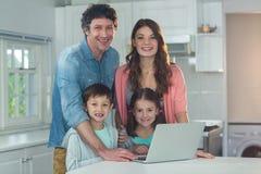 Stående av den lyckliga familjen som använder bärbara datorn arkivbilder
