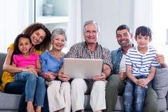 Stående av den lyckliga familjen som använder bärbara datorn på soffan fotografering för bildbyråer