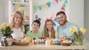 Stående av den lyckliga familjen som dekorerar ägg för påsk lager videofilmer