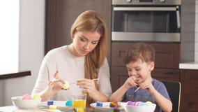 Stående av den lyckliga familjen som dekorerar ägg för påsk stock video