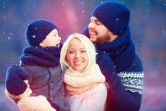 Stående av den lyckliga familjen som har gyckel under vintersnö, semesterperiod Royaltyfri Fotografi