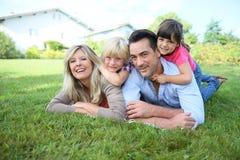 Stående av den lyckliga familjen som ligger i gräs Arkivbild