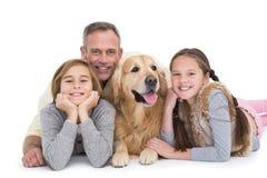 Stående av den lyckliga familjen som ligger på golvet med deras hund royaltyfria bilder