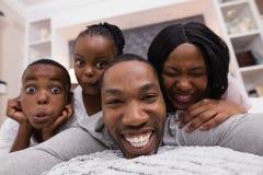 Stående av den lyckliga familjen som ligger på säng royaltyfri fotografi