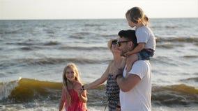Stående av den lyckliga familjen som tillsammans går runt om stranden under sommarsemester på sjösidan Stark fader Holding lager videofilmer