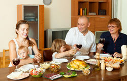 Stående av den lyckliga familjen tillsammans över att äta middag tabellen som äter fågelungen royaltyfria foton