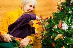 Stående av den lyckliga farmodern som kramar hennes sondotter över julklappar och dekorerat träd för nytt år som är glad arkivbilder