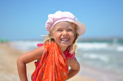 Stående av den lyckliga flickan i orange klänning på stranden Arkivfoto