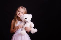 Stående av den lyckliga flickan med en mjuk björn arkivfoto