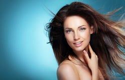 Stående av den lyckliga flickan med långt mörkt blåsa hår mot blått fotografering för bildbyråer