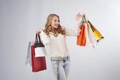 Stående av den lyckliga flickan med shoppingpåsar över vit Royaltyfria Bilder