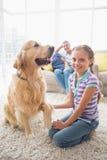 Stående av den lyckliga flickan som spelar med den hemmastadda hunden Royaltyfri Bild