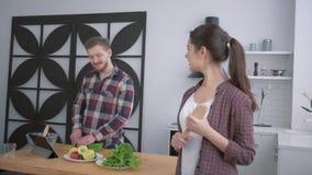 Stående av den lyckliga frun på kök, tillfredsställda kvinnablickar på maken som förbereder sunt äta från grönsaker för stock video