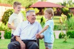 Stående av den lyckliga gamla farfadern och gulliga barn Arkivbilder