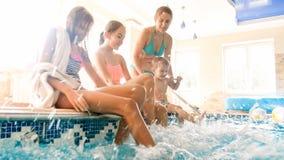 St?ende av den lyckliga gladlynta familjen som sitter p? poolsiden och plaskar vatten med fot Familj som spelar och har gyckel royaltyfri foto