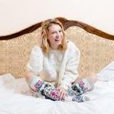 Stående av den lyckliga härliga blonda flickan för blåa ögon för ung kvinna i stucken seende kamera och att le på vit sängbakgrun Royaltyfria Bilder