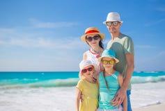 Stående av den lyckliga härliga familjen av fyra på en tropisk strand på karibisk semester Fotografering för Bildbyråer