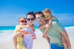 Stående av den lyckliga härliga familjen av fyra på en tropisk strand på karibisk semester Royaltyfri Foto