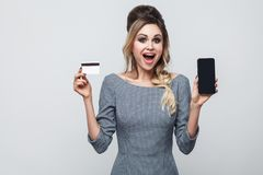 Stående av den lyckliga härliga moderna unga flickan i grått klänninganseende och att rymma mobiltelefonen och kreditkorten med d royaltyfri fotografi