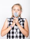 Stående av den lyckliga härliga unga flickan med söta candys iklädd nätt ung flicka en färgrik plädskjorta som rymmer Arkivbilder