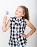 Stående av den lyckliga härliga unga flickan med söta candys iklädd nätt ung flicka en färgrik plädskjorta som rymmer Arkivbild