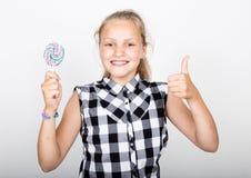 Stående av den lyckliga härliga unga flickan med söta candys iklädd nätt ung flicka en färgrik plädskjorta som rymmer Arkivfoton